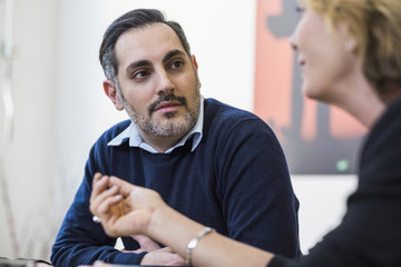 Businessman listening to female colleague in meeting at office