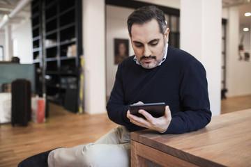 Mid adult businessman using digital tablet at desk in office