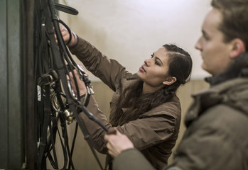 Young couple arranging bridles in horse stable