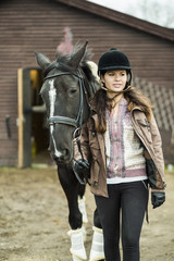 Young woman with horse walking outside barn