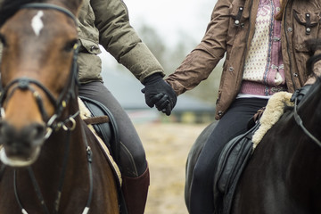 Low section of couple holding hands while riding horses