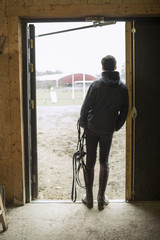 Full length rear view of young man with bridle leaning in doorway of horse stable