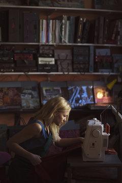 Young female fashion designer using sewing machine