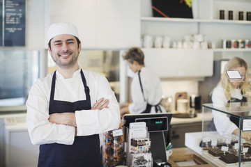 Portrait of confident owner standing arms crossed in cafe
