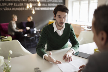 Serious businessman discussing with colleague at office desk