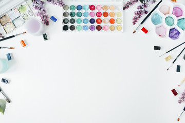 Watercolor and brushes at white background. Flat lay, top view