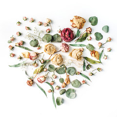 Heart made with beige roses and green leaves isolated on white background. Flat lay, top view