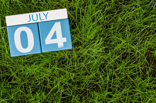 July 4th. Image of july 4 wooden color calendar on green lawn grass background. Summer day