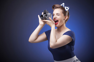 Pin Up girl taking photos with a vintage camera on blue backgrou