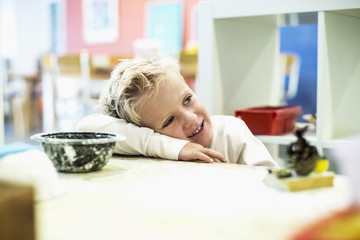 Smiling boy leaning on table in art class at kindergarten