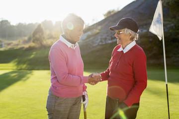 Happy senior female golfers shaking hands on golf course