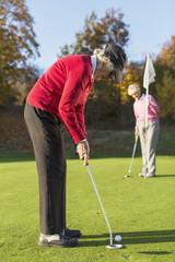 Two senior women playing golf