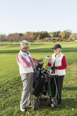 Full length of smiling senior women with golf bag on course