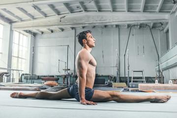 caucasian man gymnastic acrobatics equilibrium posture at gym background