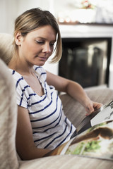 Woman looking at magazine while sitting on chair
