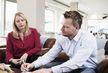 Businessman signing document while sitting with female colleague at restaurant table