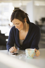 Businesswoman using smart phone while having coffee in office