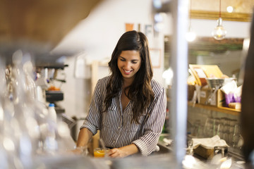 Young woman working in her own little cafe