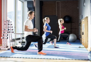 People exercising with kettlebells at gym