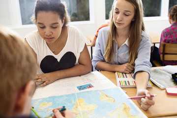 Preteen girls learning geography at school