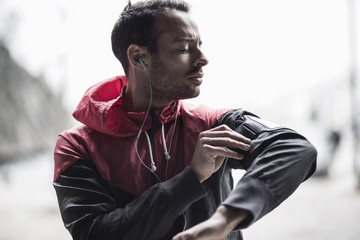 Sporty man adjusting arm band while listening to music