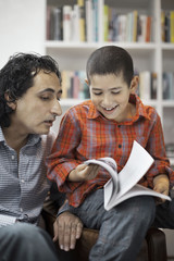 Father assisting son in doing homework at home