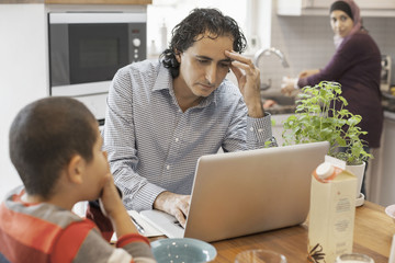 Muslim man working on laptop with family in kitchen
