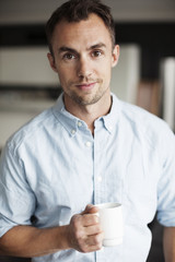 Portrait of confident businessman holding coffee mug in office