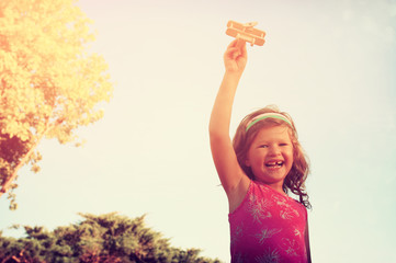 cute little girl holding wooden toy airplane against the sky