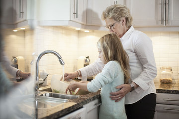 Grandmother and granddaughter washing vegetables in kitchen