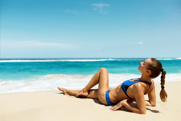 Woman On Beach In Summer. Sexy Happy Female Model Sun Tanning On Sand. Beautiful Girl With Fit Body, Healthy Tan Skin In Sport Bikini Relaxing At Luxury Sea Resort On Vacations. Summertime Relaxation