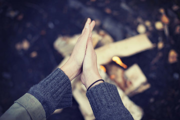 Cropped image of woman rubbing hands over campfire