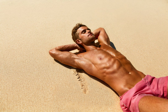 Man Body On Beach In Summer. Handsome Sexy Fit Male With Healthy Skin Sun Tan Tanning At Luxury Relax Spa Resort. Beautiful Fitness Model Relaxing, Sunbathing Lying On Sand. Summertime Travel Vacation