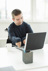 Young businessman with cerebral palsy using laptop in office