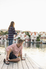 Young man looking away while woman fishing on pier at lake