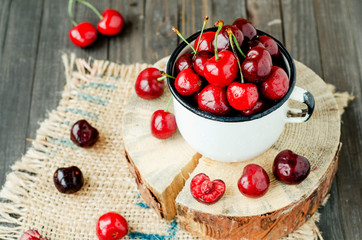 Summer berries and fruits, ripe red cherry in an iron bowl on a wooden background , rustic style