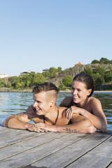 Happy couple enjoying while leaning at lake's pier