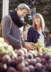 Happy couple buying vegetables at market stall