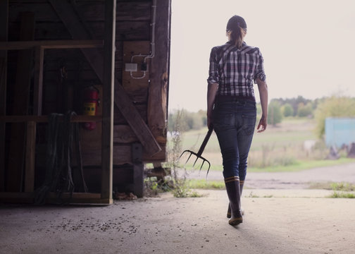 Woman holding pitchfork in barn