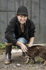 Full length portrait of female farmer petting cat against barn