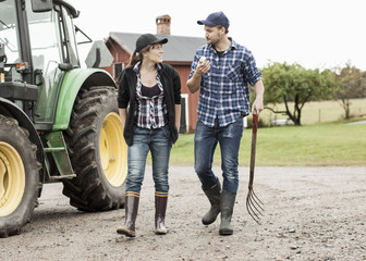 Full length of farming couple walking by tractor