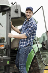 Portrait of smiling farmer entering tractor