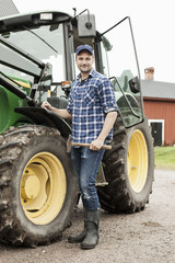 Full length portrait of farmer with hammer standing by tractor on farm