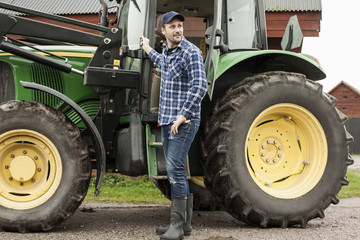 Full length of farmer standing by tractor on farm