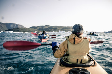 Rear view of mature woman kayaking on sea
