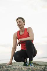 Sporty woman relaxing on rock