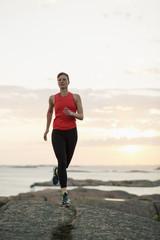 Full length of woman running on rocks at seaside