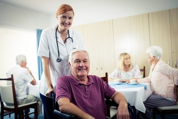 Portrait of a nurse with senior man in wheelchair