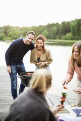 Happy friends enjoying barbecue party on pier