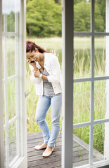 Happy woman talking on mobile phone at summer house